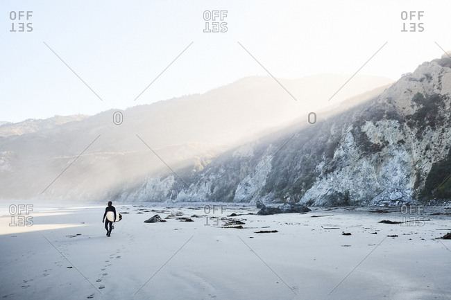 Big Sur, California - September 15, 2018: Man walking with surfboard