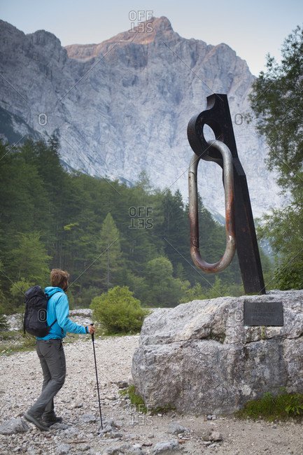 September 12, 2016: A mountain guide is walking by a monument of a giant carabiner at the base of the famous north face of the Triglav, the highest peak in Slovenia