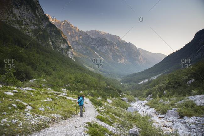 September 12, 2016: A hiker in the Vrata valley in Triglav National Park of Slovenia. In the background the Julian Alps are turning orange by the rising sun.
