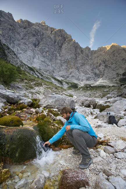 September 12, 2016: A mountain guide is tapping water from a river at the base of the famous north face of the Triglav, the highest peak in Slovenia