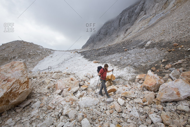 September 12, 2016: A hiker walking past a small glacier field in the moon like landscape of the summit plateau on Triglav, the highest mountain of Slovenia