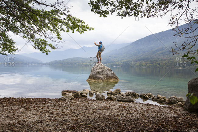 September 16, 2016: A man is taking a picture whilst standing on a rock at Lake Bohinj in Slovenia. Lake Bohinj with its surroundings is one of the top natural pearls of Slovenia. It lies within Triglav National Park enclosed by the beautiful Julian Alps. Crystal clear water offers bathing between June and September, but the area around the lake draws fans of various sport activities and pristine nature environment throughout the year.