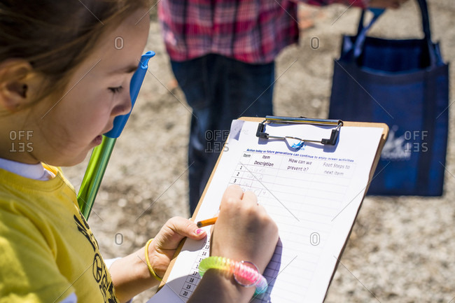 April 22, 2018: Young volunteer writing in clipboard during Earth Day beach cleanup, Portsmouth, Rhode Island, USA