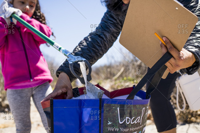 April 22, 2018: Girl picking up trash during Earth Day beach cleanup, Portsmouth, Rhode Island, USA