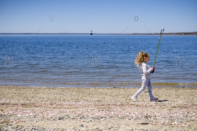 April 22, 2018: Girl walking with mechanical grabber during Earth Day beach cleanup, Portsmouth, Rhode Island, USA