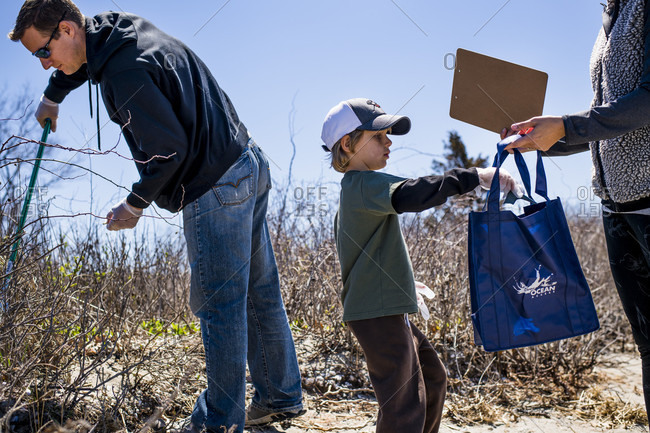 April 22, 2018: Family picking up trash during Earth Day beach cleanup, Portsmouth, Rhode Island, USA