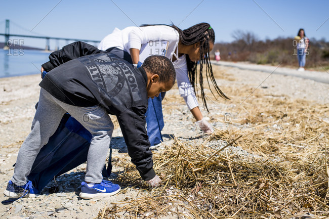 April 22, 2018: Boy and girl picking up trash during Earth Day beach cleanup, Portsmouth, Rhode Island, USA