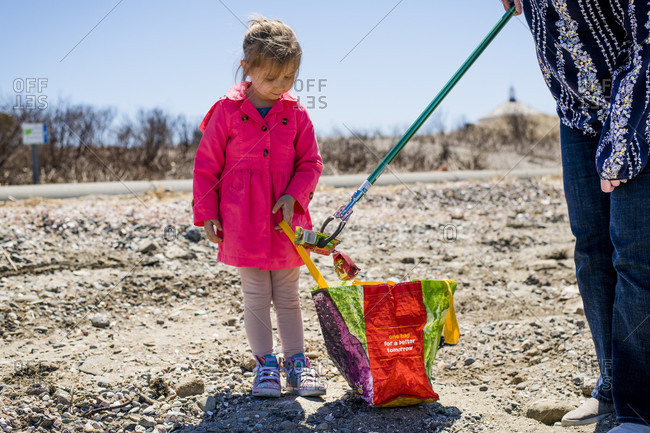 April 22, 2018: Girl and adult picking up trash during Earth Day beach cleanup, Portsmouth, Rhode Island, USA