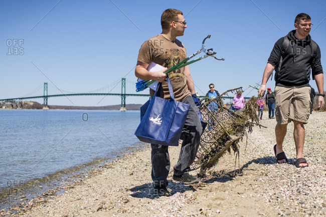 April 22, 2018: Two men carrying mechanical grabber, trash bag and garbage during Earth Day beach cleanup, Portsmouth, Rhode Island, USA