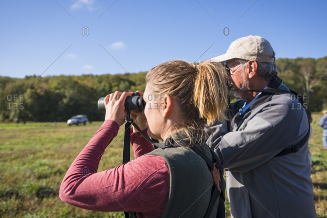 October 5, 2016: Woman and senior man bird watching with binoculars with Audubon Society, Johnston, Rhode Island, USA