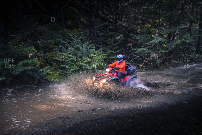 February 15, 2015: Side view of adventurous man driving quadbike through mud on dirt road in forest, Callaghan Valley, Whistler, British Columbia, Canada