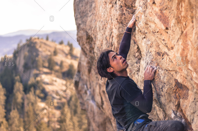 April 4, 2015: Side view shot of adventurous rock climber climbing cliff at Skaha Bluffs, Penticton, British Colombia, Canada