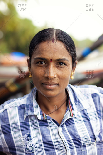 August 28, 2017: Head and shoulders portrait of mature woman with black hair looking at camera, Kerala, India