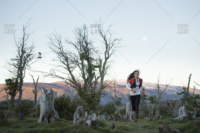 April 6, 2017: Front view shot of woman trail running in Torres del Paine National Park, Magallanes region, Chile