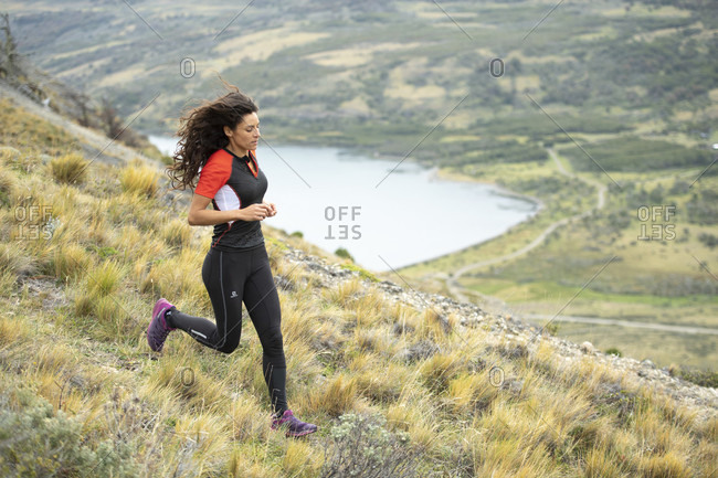 April 9, 2017: Side view shot of woman trail running in natural setting in Torres del Paine National Park, Magallanes region, Chile