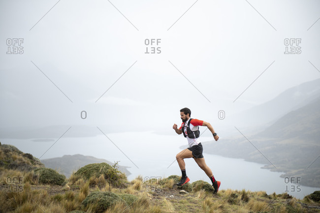 April 9, 2017: Side view shot of man trail running in natural setting in Torres del Paine National Park, Magallanes region, Chile