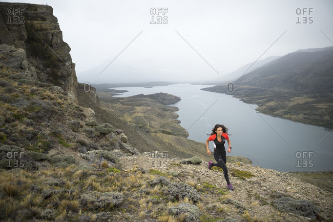 April 9, 2017: Front view shot of woman trail running in natural setting in Torres del Paine National Park, Magallanes region, Chile