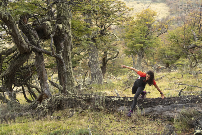 April 9, 2017: Woman jumping over log while trail running in Torres del Paine National Park, Magallanes Region, Chile