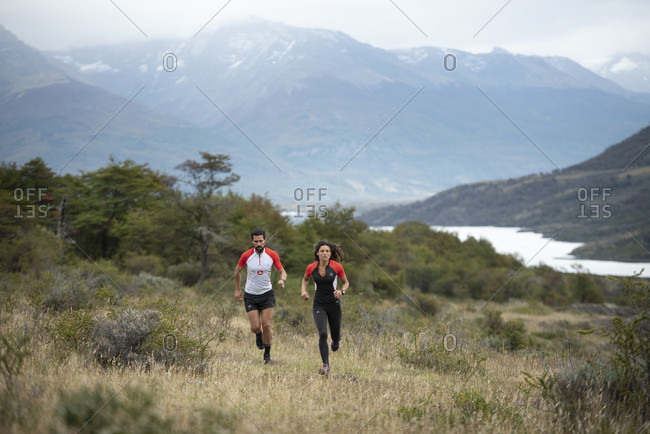 April 9, 2017: Front view shot of man and woman trail running in Torres del Paine National Park, Magallanes Region, Chile
