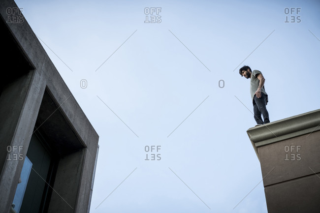 January 8, 2017: View from below of male parkour athlete standing on roof