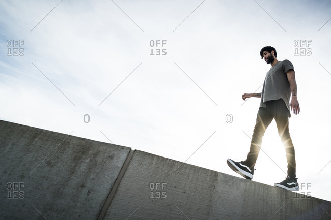 January 8, 2017: Side view of male parkour athlete walking on top of wall