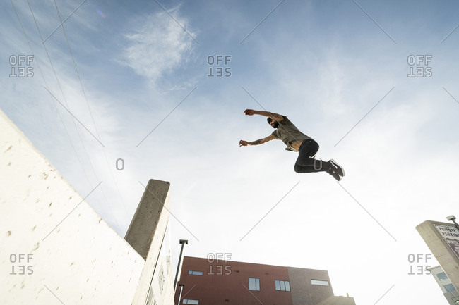 January 8, 2017: Side view of single male parkour athlete jumping from one wall to another