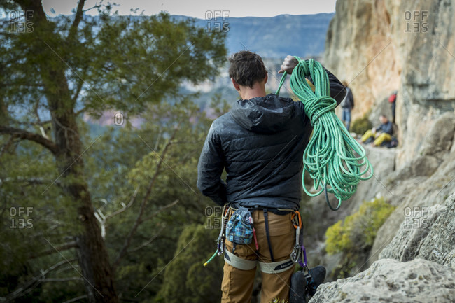 February 18, 2018: Rear view shot of male rock climber carrying rope to cliff, Siurana, Catalonia, Spain