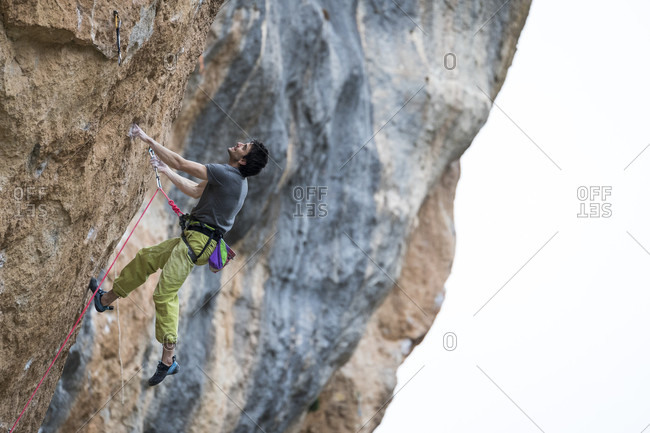 March 4, 2018: Side view of single adventurous man rock climbing up cliff, Siurana, Catalonia, Spain