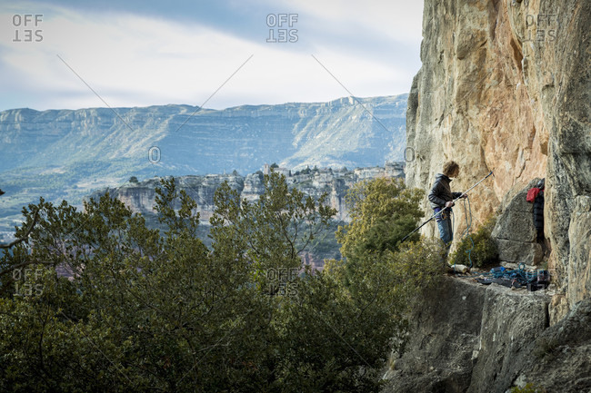 February 18, 2018: Distant view of single adventurous male rock climber preparing stick clip at cliff, Siurana, Catalonia, Spain