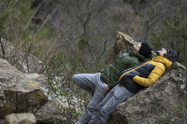 March 4, 2018: Side view of two men in jackets lying on back against rock and looking up