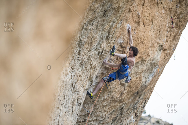March 4, 2018: Side view of single shirtless rock climber climbing challenging cliff, Siurana, Catalonia, Spain