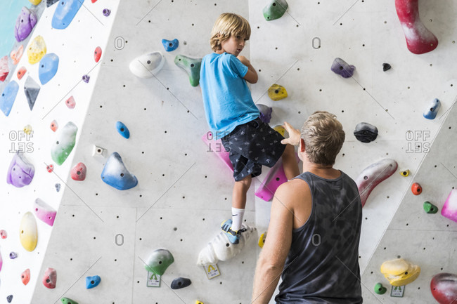 March 21, 2018: Rear view shot of father helping son with climbing wall