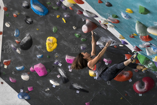 March 31, 2018: Side view of single adventurous woman climbing on overhanging wall