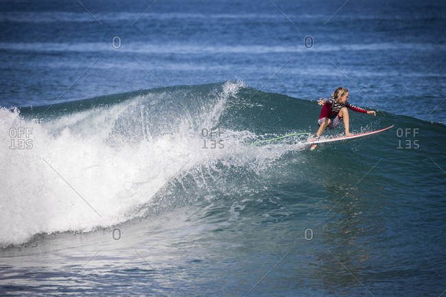 March 25, 2018: Side view shot of single boy surfing in sea