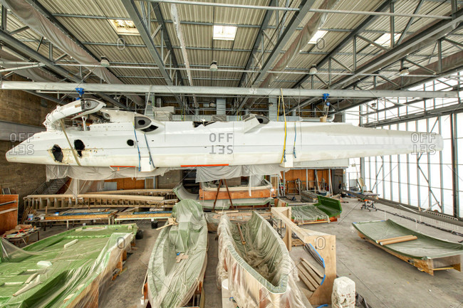 April 10, 2018: Trimaran racing yacht suspended from roof of a boat shed, Keroman, Submarine Base, Lorient, Morbihan, Brittany, France.