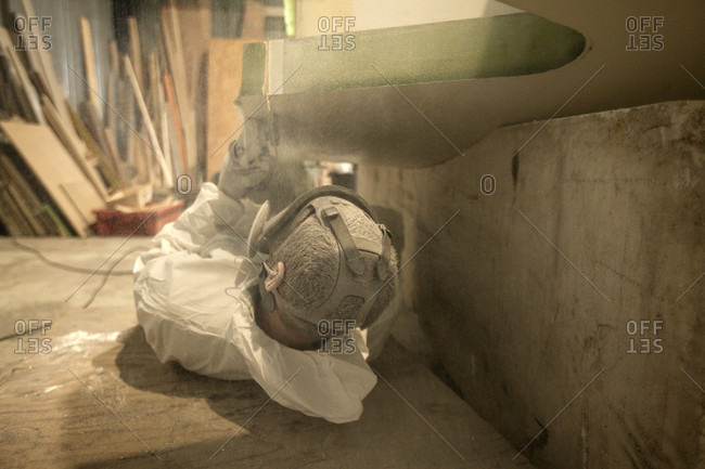 May 10, 2018: A trademan is using a grinder for cutting some extra composite material on a sailing yacht hull for the preparation of the Lift 40 ( Class 40 ) for the skipper, Gepeto Composite, Lorient Keroman Submarine Base, Brittany, France