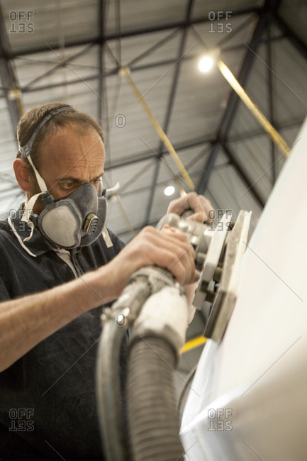 May 10, 2018: A trademan is using a sanding machine for removing the rough surfaces on a sailing yacht hull for the preparation of the Lift 40 ( Class 40 ) for the skipper, Gepeto Composite, Lorient Keroman Submarine Base, Brittany, France