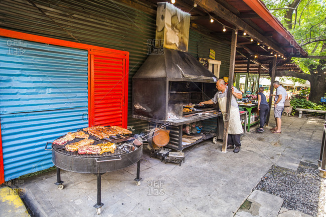 November 8, 2017: Grillmaster turning meat on grill, Buenos Aires, Argentina