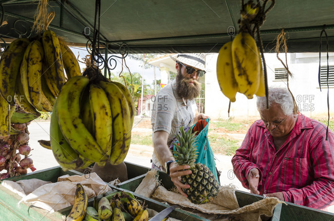 May 18, 2015: Man with beard buying fruit from market stall, Vinales, Pinar del Rio Province, Cuba