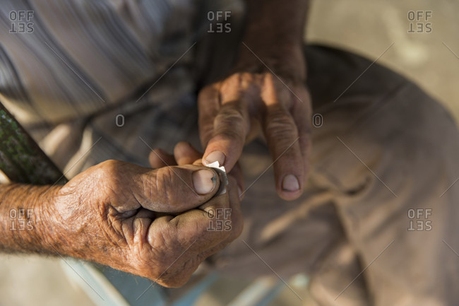 March 4, 2017: Close up shot of man cleaning fingernails with razor blade, Vinales, Pinar del Rio Province, Cuba