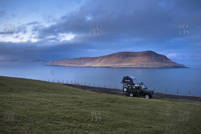 March 18, 2016: Side view of 4x4 car driving along coastline, Faroe Islands, Denmark