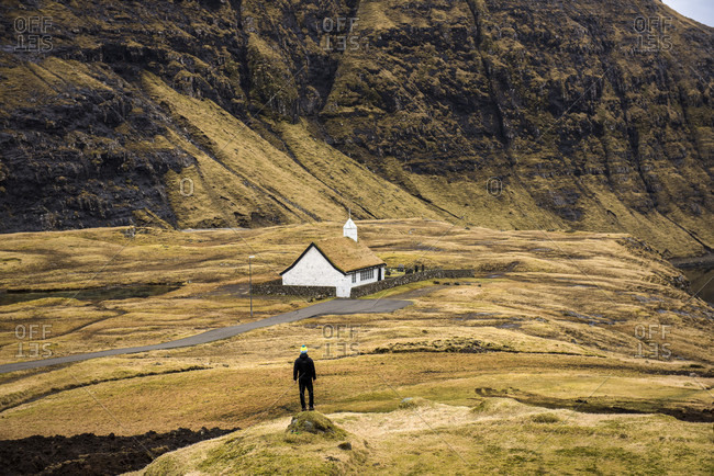 March 18, 2016: Rear view of man standing near sod roof house, Faroe Islands, Denmark