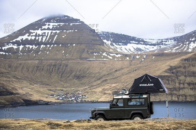 March 21, 2016: Side view of single 4x4 car with tent parked against mountains, Faroe Islands, Denmark