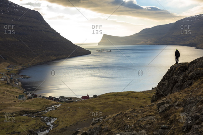 March 19, 2016: Distant view of man standing on seashore, Faroe Islands, Denmark
