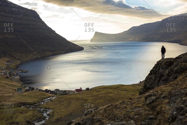 March 19, 2016: Distant view of man standing on seashore, Faroe Islands, Denmark