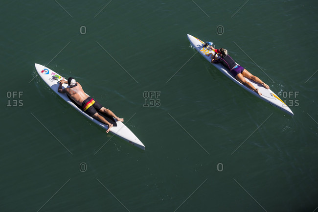 April 24, 2016: View from above of two paddleboarders lying on paddleboards