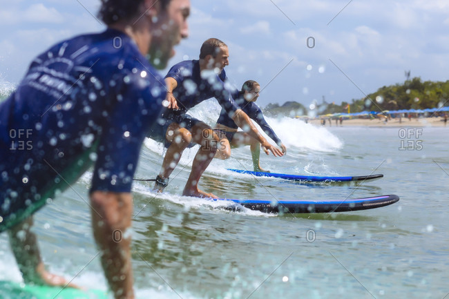 September 18, 2017: Side view of three adventurous surfers riding wave in sea