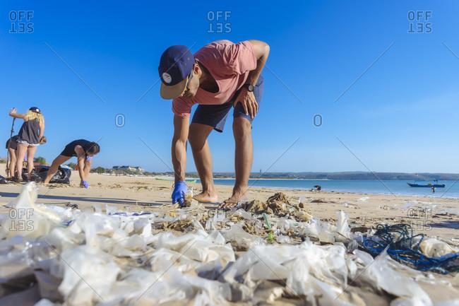 September 18, 2017: Man bending while picking up trash at beach, Jimbaran, Bali, Indonesia