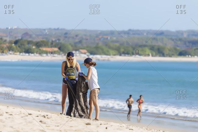 September 18, 2017: Two young women picking up trash at beach, Jimbaran, Bali, Indonesia