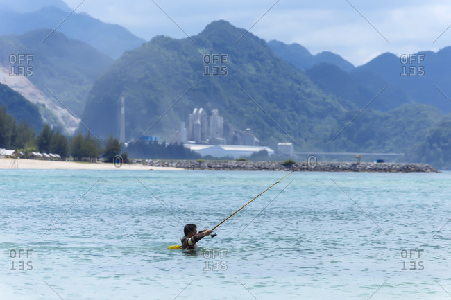 January 29, 2018: Side view of fisherman neck deep in sea with fishing rod, Banda Aceh, Sumatra, Indonesia